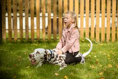 Smiling, singing little girl hugging a big dog in meadow,games outdoor.Happy child loves her pet. Positive photo of royalty free stock image