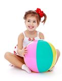 Smiling little girl hugging a big inflatable ball Stock Photo