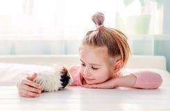 Smiling little girl hugging guinea pig Royalty Free Stock Photo