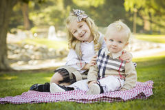 Smiling Little Girl Hugs Her Baby Brother at the Park. Sweet Little Girl Hugs Her Baby Brother on a Picnic Blanket Outdoors at the Park Stock Image