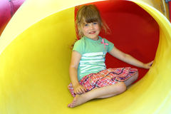 Smiling little girl inside yellow plastic tube Stock Images