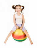 Smiling little girl jumping on a big ball Stock Photography