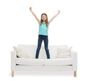 Smiling little girl jumping or dancing on sofa Stock Photography