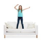 Smiling little girl jumping or dancing on sofa. Home, leisure and happiness concept - smiling little girl jumping or dancing on sofa Stock Image