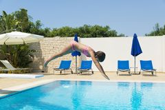 Smiling little girl jumping in an outdoor pool in summer. Smiling little girl jumping head to dive in a swimming pool of a resort hotel in summer in Sicily royalty free stock photography