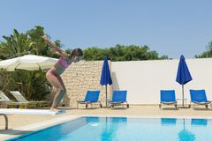 Smiling little girl jumping in an outdoor pool in summer. Smiling little girl jumping head to dive in a swimming pool of a resort hotel in summer in Sicily stock photo