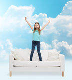 Smiling little girl jumping on sofa Royalty Free Stock Photo