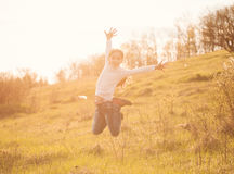 Smiling little girl jumping on sunlight in countryside. On a hill Stock Photo