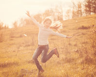 Smiling little girl jumping on sunlight in countryside. On a hill Royalty Free Stock Photography