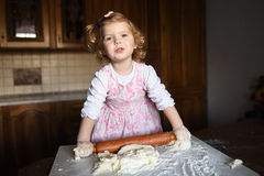 Smiling little girl kneading the dough Royalty Free Stock Photo