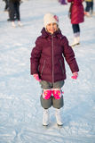 Smiling little girl in knee pads skating. At the rink in winter royalty free stock photo