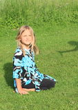 Smiling little girl kneeing on grass Royalty Free Stock Photography