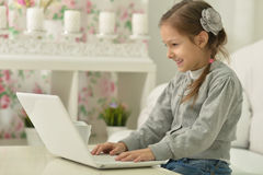 Smiling little girl with laptop computer Royalty Free Stock Image