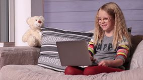Smiling little girl with laptop computer at home stock video footage