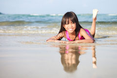 Smiling little girl laying  on the beach Stock Photography