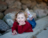Smiling Little Girl Laying on Curb Stock Image