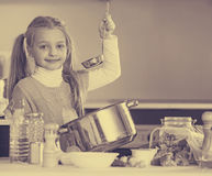 Smiling little girl learning to cook in kitchen Royalty Free Stock Image