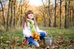 Smiling little girl with leaves and bucket Royalty Free Stock Images