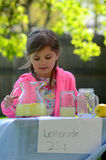Smiling little girl at lemonade stand in summer. Smiling little girl with braids and pink jacket at her lemonade stand Royalty Free Stock Photography
