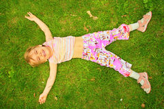 Smiling little girl lies on back on grass. A smiling little girl lies on back on grass Stock Photography