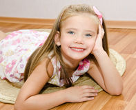 Smiling little girl lies on a house floor Stock Images