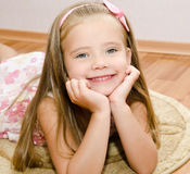 Smiling little girl lies on a house floor Royalty Free Stock Images
