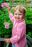 Smiling little girl with lilac bush Royalty Free Stock Photos