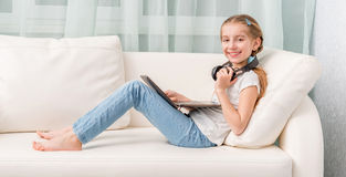 Smiling little girl listening something with headphones looks at camera. Smiling little girl listening something with headphones and note book on sofa looks at Royalty Free Stock Images