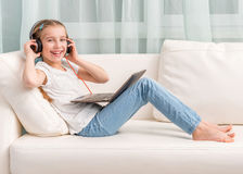Smiling little girl listening something with headphones looks at camera Stock Photo