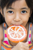 Smiling little girl with a lollipop. Closeup smiling little girl with a lollipop Royalty Free Stock Photos