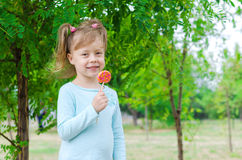 Smiling little girl with a lollipop, free space. Beautiful girl Royalty Free Stock Images