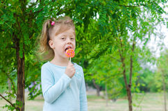 Smiling little girl with a lollipop, free space. Beautiful girl Stock Photography