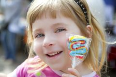 Smiling little girl with lollipop sweet in hand Stock Photography