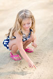 Smiling little girl with long blond hair squatting and drawing in the sand Stock Images