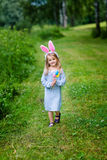 Smiling little girl with long blond hair wearing rabbit ears Royalty Free Stock Photography