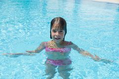 Smiling little girl looking at camera in an outdoor pool. In summer royalty free stock image