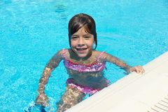 Smiling little girl looking at camera in an outdoor pool. In summer stock photo