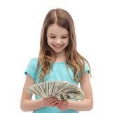 Smiling little girl looking at dollar cash money Stock Photography