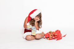 Smiling little girl is looking at an inappropriate gift royalty free stock photography
