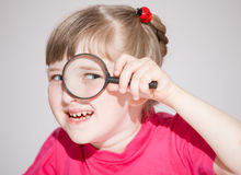Smiling little girl looking through a loupe Stock Photography