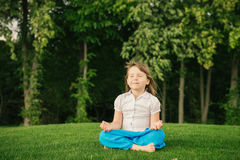 Smiling little girl in lotus position Royalty Free Stock Photo