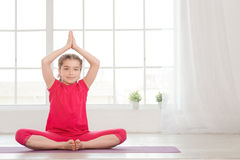 Smiling little girl in lotus position Royalty Free Stock Photography