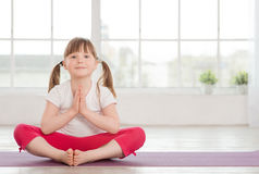 Smiling little girl in lotus position Stock Photography