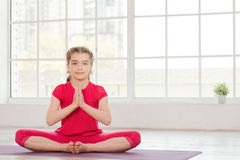 Smiling little girl in lotus position Stock Photos