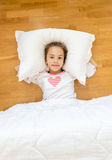Smiling little girl lying on big pillow on floor Stock Images