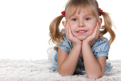 Smiling little girl lying on the carpet Royalty Free Stock Photography