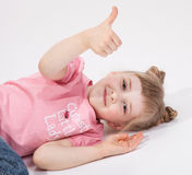 Smiling little girl lying on the floor and showing thumb up. White background Royalty Free Stock Images