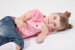 Smiling little girl lying on the floor and showing thumb up. White background Stock Image