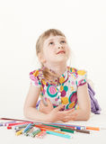 Smiling little girl lying on the floor and thinking Stock Photos