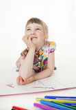 Smiling little girl lying on the floor and thinking Royalty Free Stock Photo